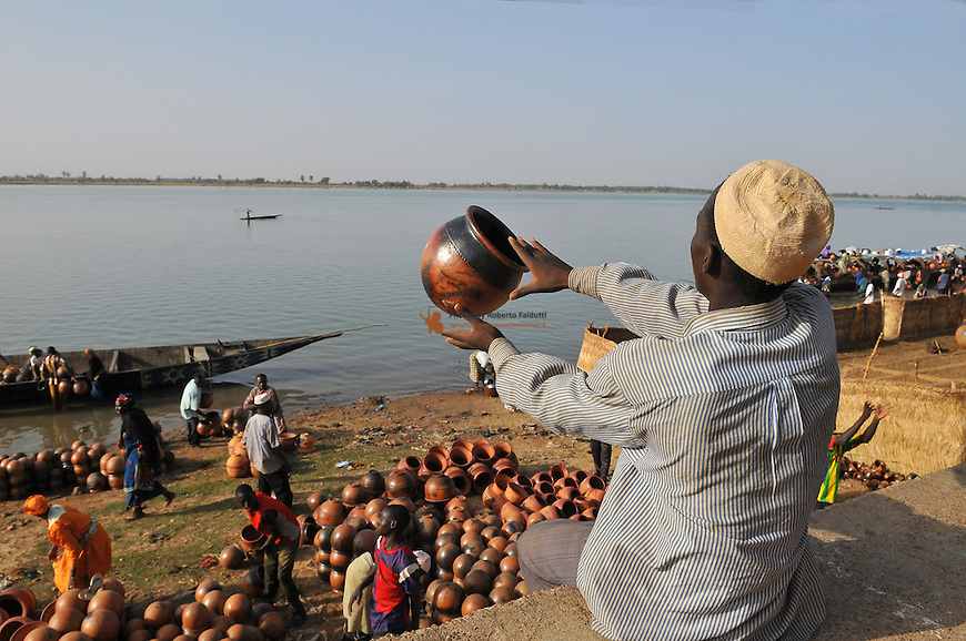 Hand made pottery being unloaded from a barge onto the bank of the Niger river in Mali