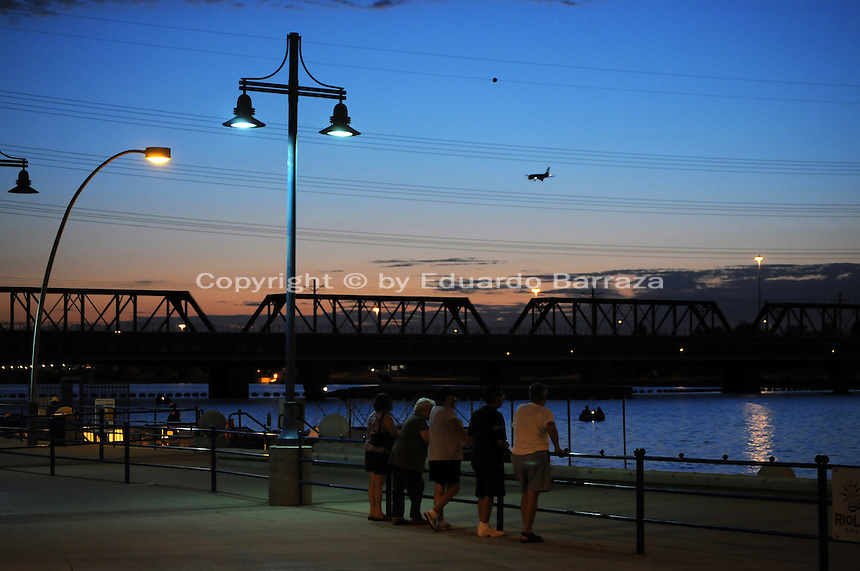 Tempe, Arizona. A group of people at Tempe Town Lake enjoys a sight of the lake just after sunset. The lake is a favorite spot for residents and visitors. The airplane seen flying is about to land at nearby Phoenix Sky Harbor International airport. The Light Rail bridge is seen in the background. Photo by Eduardo Barraza © 2015