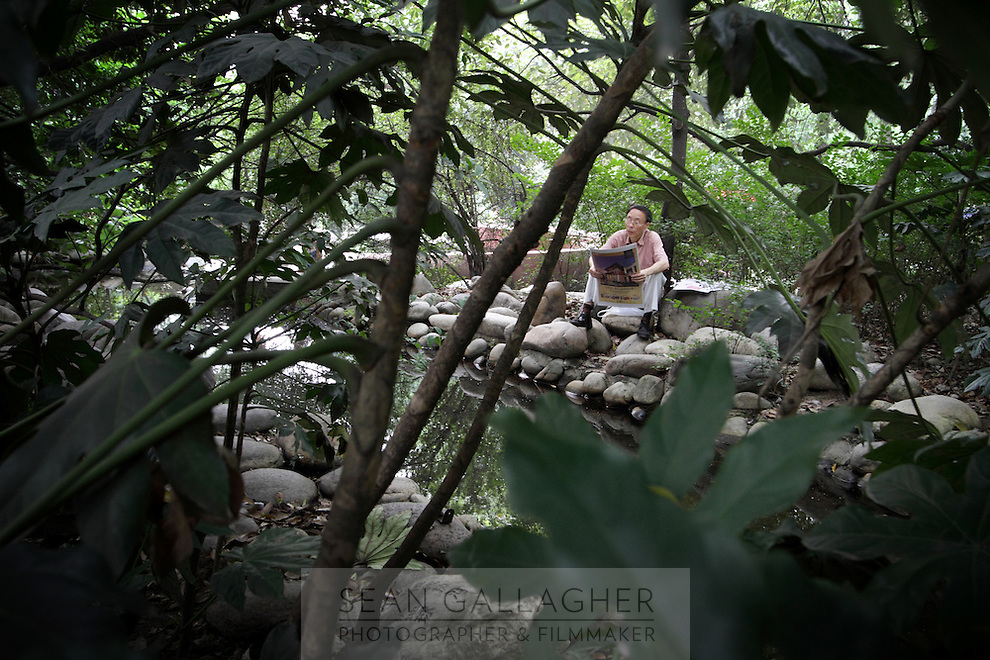 "A man reads a newspaper in the ""Living Water Garden"" in Chengdu, Sichuan Province. The garden is a park aimed at highlighting the importance of the relationship between man and water. 2010"