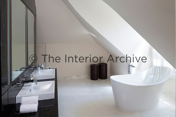 The master bathroom is decorated in neutral tones and features a stylish free standing bath in the centre of the room. Two washbasins with mirrors above are set in a bespoke bronze tile surround.