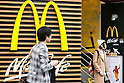 December 24, 2015, Tokyo, Japan - Pedestrians walk past a poster announcing the closing of McDonald's largest store in Japan located in Harajuku on January 15, 2016. McDonald's is reportedly looking to sell 15% to 33% of shares of its Japanese subsidiary and gain 100 billion yen ($817 million). McDonald's Holdings Japan is expected a net loss of 38 billion yen during its fiscal year ending on December 31, after scandals of expired chicken in the summer of 2014 and contamination with foreign objects in January 2015. (Photo by Rodrigo Reyes Marin/AFLO)