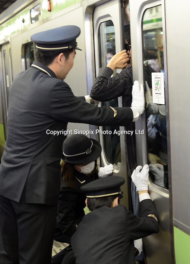 Railway staff  try to release a mans arm trapped by a door on a full train during rush hour, Shinjuku Station, Tokyo, Japan. With up to 4 million passengers passing through it every day, Shinjuku station, Tokyo, Japan, is the busiest train station in the world. The station was used by an average of 3.64 million people per day.  That&rsquo;s 1.3 billion a year.  Or a fifth of humanity. Shinjuku has 36 platforms, and connects 12 different subway and railway lines.  Morning rush hour is pandemonium with all trains 200% full. <br /> <br /> Photo by Richard jones / sinopix