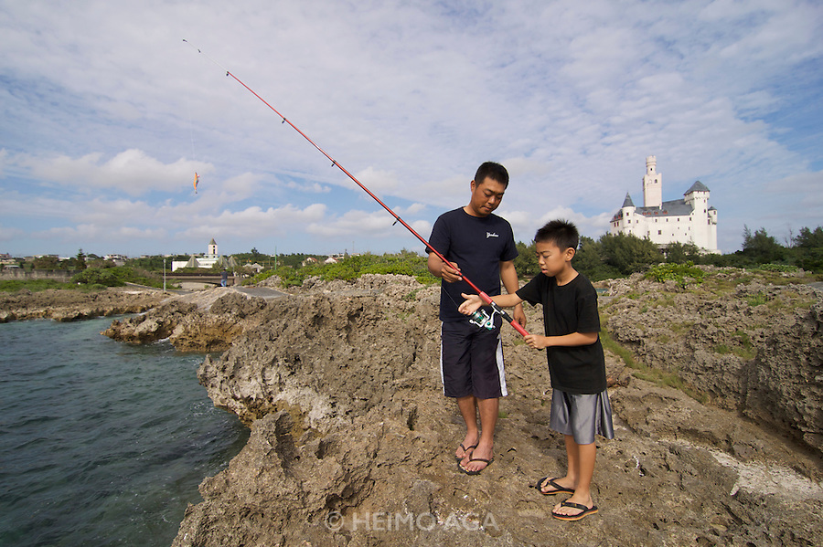 Miyako-jima. Ueno German Culture Village. Fishing in front of a replica of the Marksburg, a castle situated on a rock in the Rhine river.
