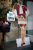 A cutout advertisement of an Indian model for Kingfisher is seen in a show-window of a travel agency in Mumbai, India.