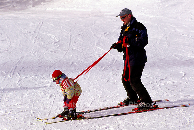 A Young Child learning to Downhill Ski with Father holding Harness, at Big White Ski Resort near Kelowna, in the Thompson Okanagan Region, British Columbia, Canada