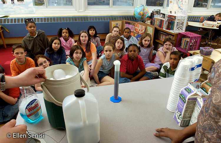 MR / Schenectady, NY.Yates Arts-in-Education Magnet School (urban elementary school) .Grade 4.Students watch chemical reaction in graduated cylinder in experiment set up by science mentor (materials scientist at research center, full-time working mom) in their classroom. Mentor volunteers weekly to demonstrate and explain scientific concepts..Here, a basic solution is being converted to an acidic solution as carbon dioxide [dry ice] is added to a base (ammonia in water [Windex ®]) .to create carbonic acid..MR: g4m.© Ellen B. Senisi