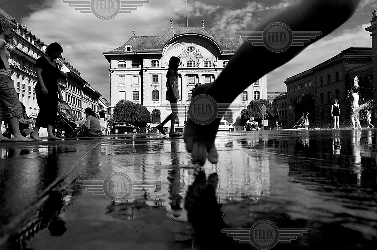 Children play in the water fountains that spout in front of the Swiss National Bank building on Bundesplatz (Parliament Square). /Felix Features