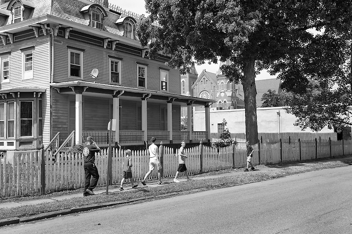 A family of five walking down a street with a Victorian house and a Large Church in the Back Ground