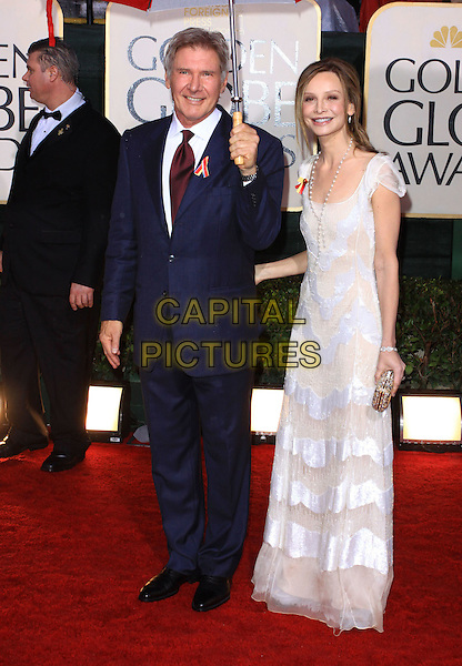 HARRISON FORD & CALISTA FLOCKHART.67th Golden Globe Awards held Beverly Hilton, Beverly Hills, California.17th January 2010..arrivals globes full length couple white dress blue suit tie red sheer striped clutch bag beads necklace long maxi umbrella raining .CAP/ADM/KB.©Kevan Brooks/Admedia/Capital Pictures