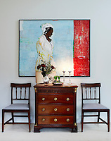 A painting by Morten Affelhoy hangs above the mahogany chairs and chest of drawers in the living room