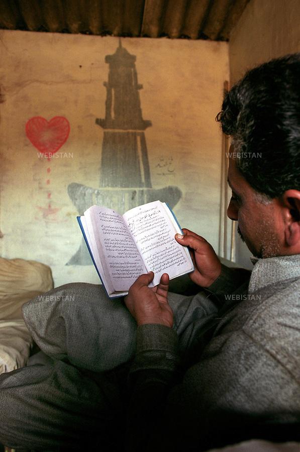 Pakistan.Gaddani. 2005. A worker reads his religious book in his quarter of the ship-breaking yard...Pakistan.Gaddani. 2005. Un ouvrier lit son livre religieu dans ses quartiers du chantier de démantèlement des bateaux