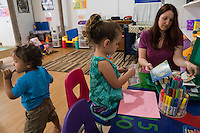 Lora Reyes is a licensed family childcare educator in Westfield, Mass., where she operates the daycare Lora's Little Ones out of her home on Thurs., June 2, 2016. Here she helps kids at the art and writing station as they make cards. Today she was in charge of 7 children, aged 14 months to 5 years old, handling meals, playtime, and educational activities throughout the day, starting about 7am and going until 4:30pm. She uses the Mother Goose Time curriculum throughout the day. Reyes is currently pursuing an undergraduate degree in Psychology at Holyoke Community College. She started 2 years ago after earning a Child Development Associate certification.