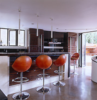 This slick contemporary kitchen has a polished concrete floor and leather bar stools