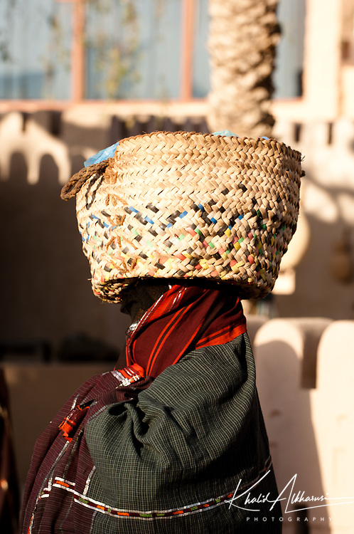 Old Woman form A'Sharqiya north Governorate carrying Handle Storage Basket is made from date palm.