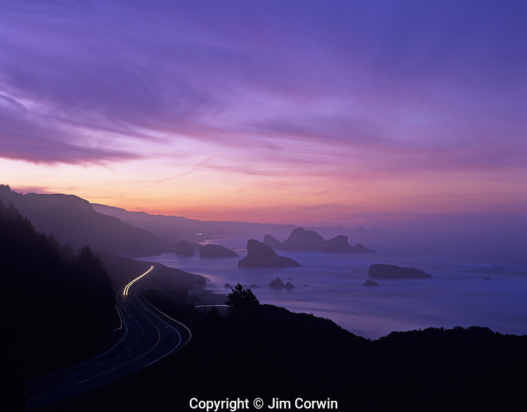 Cape Sebastian State Park Southern Oregon Coast Highway 101 at sunrise looking south from viewpoint above coastline with rock formations and beach with car streaks Oregon State USA