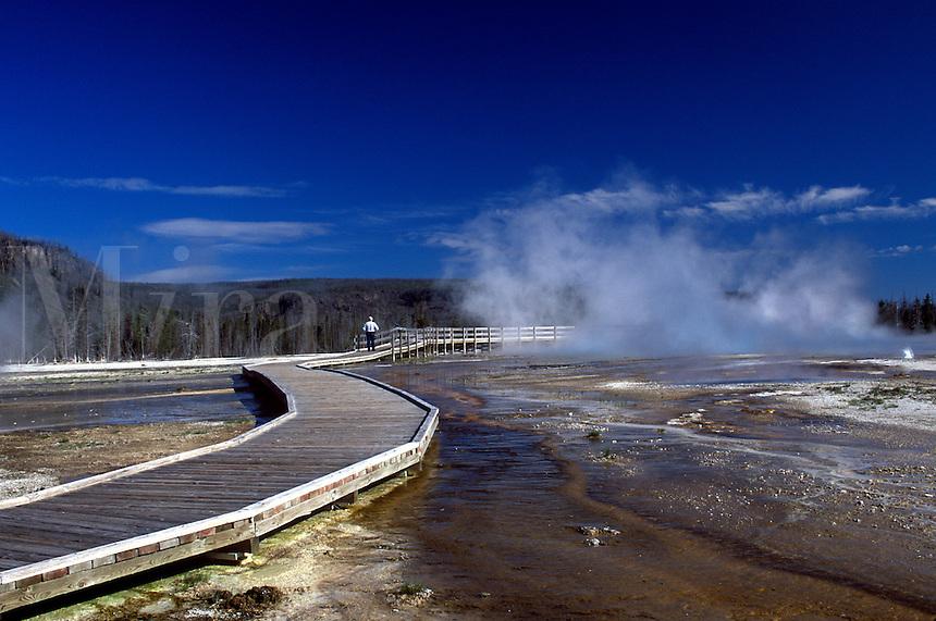 Boardwalk through Black Sand Basin with steam rising.