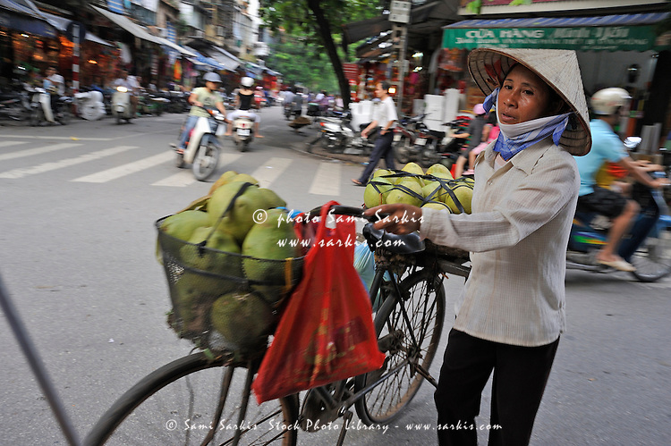 Woman selling / carrying fruit in Hanoi city centre, Vietnam