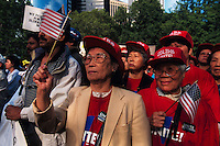 (970522-SWR03)--File Photo -- New York, NY -- A group of Asian immigrants wearing red Unite t-shirts and red Local 23-45 baseball caps wave an American flag. Thousands of immigrants gathered in Battery Park, in the shadow of the Statue of Liberty and Ellis Island, for a Rally for Immigrants Rights.  Photo © Stacy Walsh Rosenstock