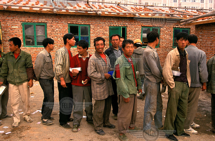 ©Mark Henley/Panos Pictures..China, Liaoning, Dalian Development Zone..MIgrant labourers on construction site queuing for lunch outside their dormitories.