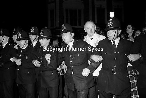 Father Michael Hollings at this time Roman Catholic parish priest of St Mary of the Angels. Notting Hill Carnival riot 1979 London UK. Police cordon off All Saints Road.