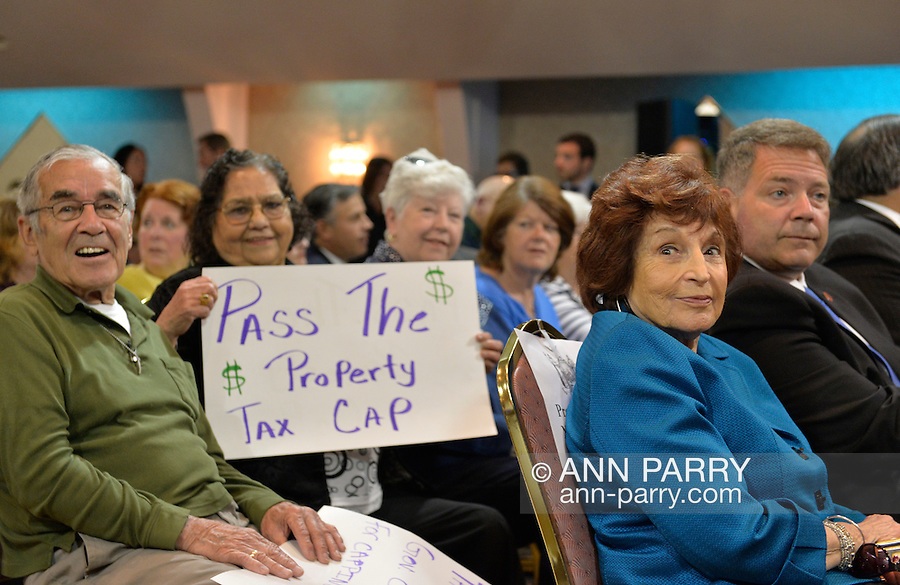 Seaford, New York, USA. 3rd June 2015. At far right, Nassau County Legislature Presiding Officer NORMA GONSALVES (Rep. - East Meadow, LD 13), and Legislator STEVEN RHOADS (Rep. - Bellmore, LD 19), and senior citizens with Pass The Property Tax Cap posters are among those attending Press Conference supporting extension of the NY Property Tax Cap. At the bi-partisan event at Knights of Columbus Hall, over a hundred area residents and officials, and the governor, urged extending the property tax cap before the state legislative session ends on June 17. The NY Property Tax Cap is set to expire June 2016, but is legally linked to NYC rent-control regulations set to expire this month.