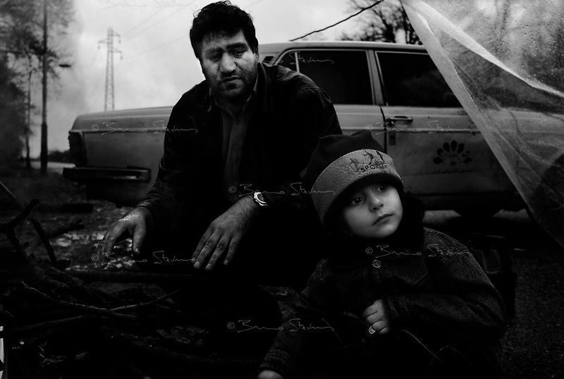 near Nour, Iran, March 27, 2007.A family on holiday in the region tries to warm up by a small fire in a park where they are camping on a cold, rainy day...Roghieh,5, with her father.