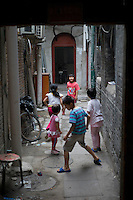 Chinese children play at a Hutong, or traditional alleyway, in Qianmen Street area of Beijing on June 1, 2012. Qianmen Street area has a history of more than 570 years. The shopping area was called Zhengyangmen Street during the Ming and Qing Dynasties, and finally named Qianmen Street in 1965. (Leica M9, 50mm f2)