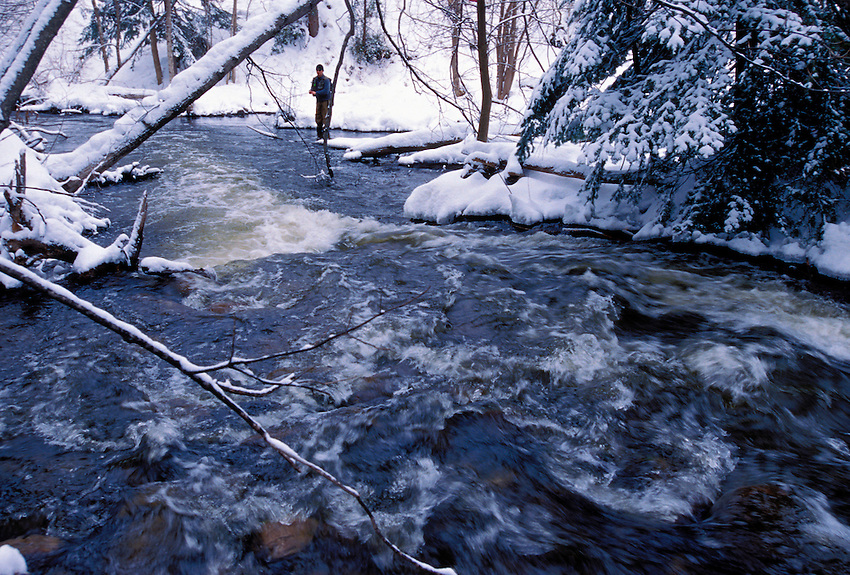 A MAN FLY FISHES FOR STEELHEAD ON THE CARP RIVER NEAR MARQUETTE, MICHIGAN FOLLOWING A SNOW STORM.