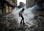 A demonstrator smothers a tear gas canister in a muddy puddle of water during November 25, 2012, protests in and around Cairo's Tahrir Square. The protestors were upset by Egyptian President Mohammed Mursi's November 22nd decision to assume sweeping new powers.