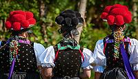 Deutschland, Baden-Wuerttemberg, Ortenaukreis, Kirnbach (Wolfach): drei junge Frauen auf dem Kirnbacher Bollenhut-Talwegle in der beruehmten Kirnbacher Tracht mit dem roten und schwarzen Bollenhut, die heute in der ganzen Welt als Schwarzwaelder Tracht bekannt ist - Rueckansicht | Germany, Baden-Wurttemberg, Kirnbach (Wolfach): three young women in famous Black Forest costume with red and black Bollenhat - back view