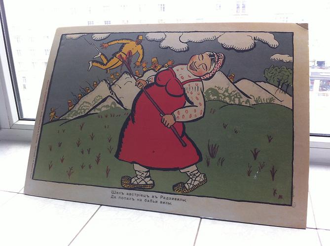 """Ansichtskarte mit Karikatur aus dem Ersten Weltkrieg in den Moskauer Redaktionsräumen des """"Projekts 1917"""" - """"Ging ein Österreicher nach Radzivily, da fiel er auf der Bäuerin Mistgabel."""""""