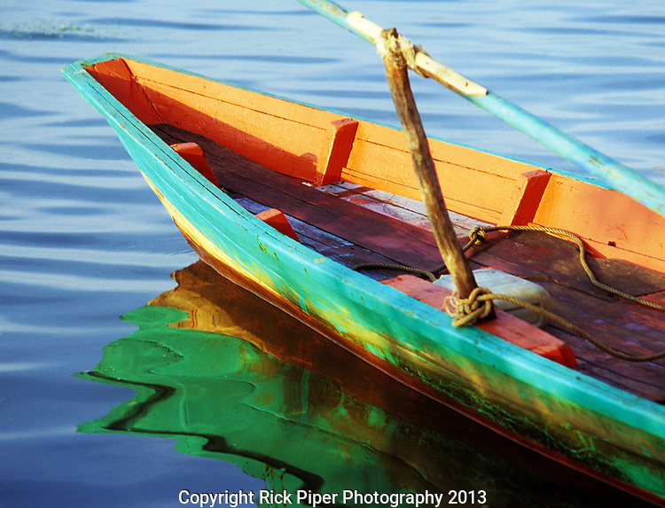 Kampot Boat 01 - Reflections of a traditional Cham rowing boat on the Sanke river, Kampot, Cambodia