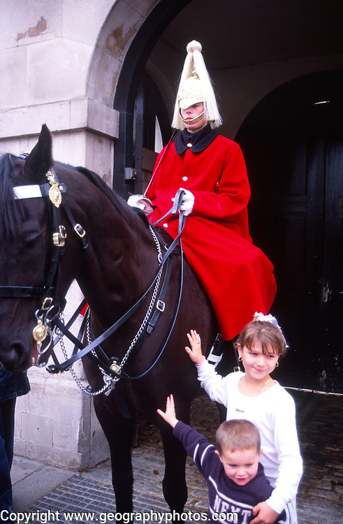 ATBK84 Two children pose by Horse guard soldier and horse Whitehall London England