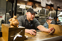Sous chef Chris Drown checks order tickets at the expediter station in the kitchen at Hojoko, a Japanese bar and restaurant in The Verb Hotel in the Fenway neighborhood of Boston, Massachusetts, USA, on Friday, Dec. 4, 2015.The restaurant serves food as it is ready, rather than all at once; chefs check off dishes as they are completed and handed off to waiters.