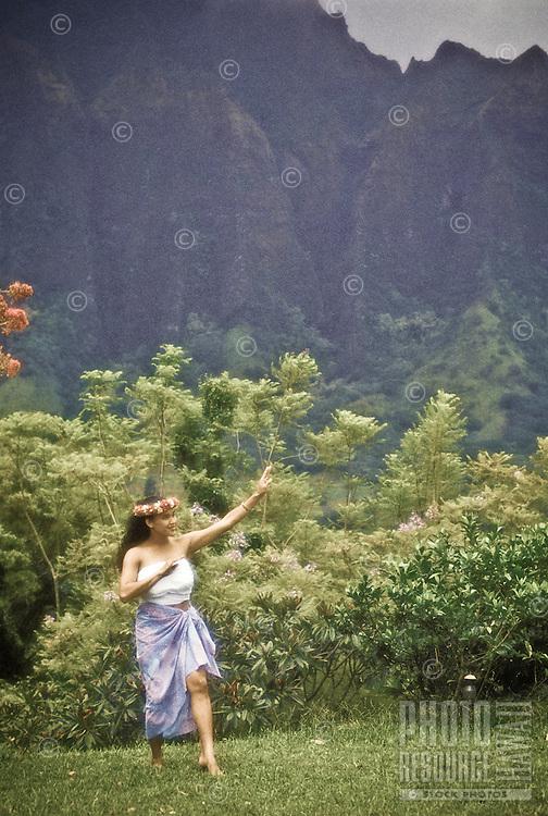 Hawaiian woman dancing the hula near the Koolau mountains