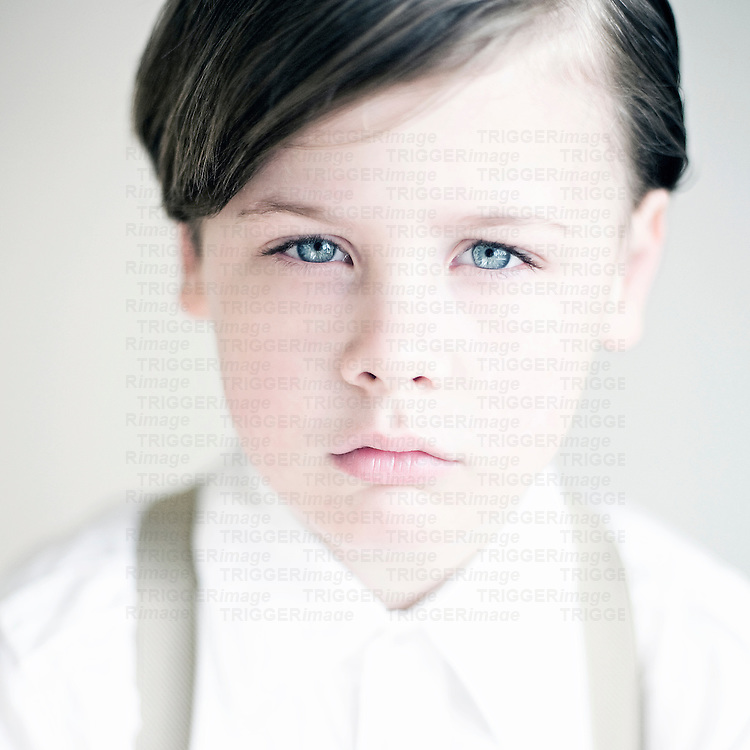 Close up of a young boys face with blue eyes looking at camera