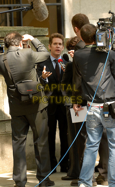 """TOM HOLLANDER.Filming on the set of """"In The Loop"""" (an American / BBC production about Bush & Blair starting a war) on location behind The British Museum, London, england..May 13th, 2008.full length black suit film movie reporters photographers press interview.CAP/IA.©Ian Allis/Capital Pictures."""