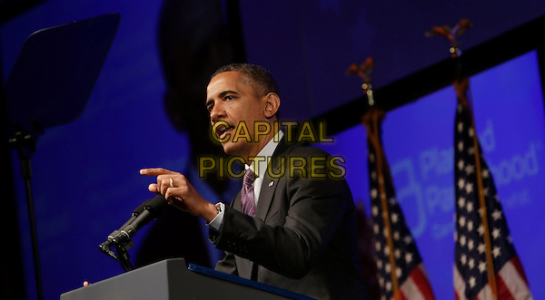 Barack Obama.United States President Barack Obama speaking at the Planned Parenthood Gala at the Washington Marriott Wardman Park Hotel in Washington, DC, USA, April 26, 2013..half length podium American flags  suit tie speaking  purple politics microphone side hand finger .CAP/ADM/CNP/CK.©Chris Kleponis/AdMedia/Capital Pictures