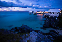 Night shot of the small wooden houses placed on stilts on top of the water in the Seven Beaches resort in Bermuda, Atlantic Ocean