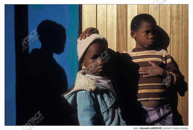 These children live in an extended household led by their crippled grandmother. Some of the children attend the Dula Sentle orphanage during the day.  Since Botswana has no orphanages where children can board, at the end of the day, the children return home to their grandmother's hut. In Botswana, to give a child away is shameful and unthinkable to family, regardless of the consequences. Otse, Botswana, August 2003...2003 © Kenneth JARECKE (CONTACT Press Images)
