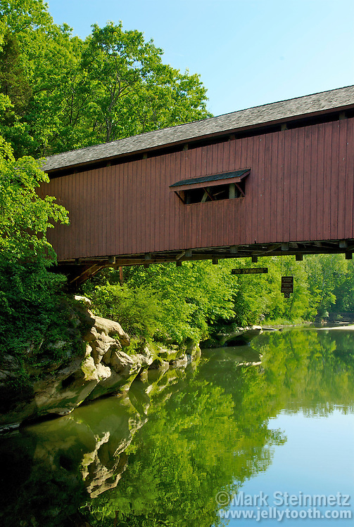 View looking downstream at the Narrows Covered Bridge, built in 1883 by Joseph A. Britton, over Sugar Creek in Parke County, Indiana, USA.