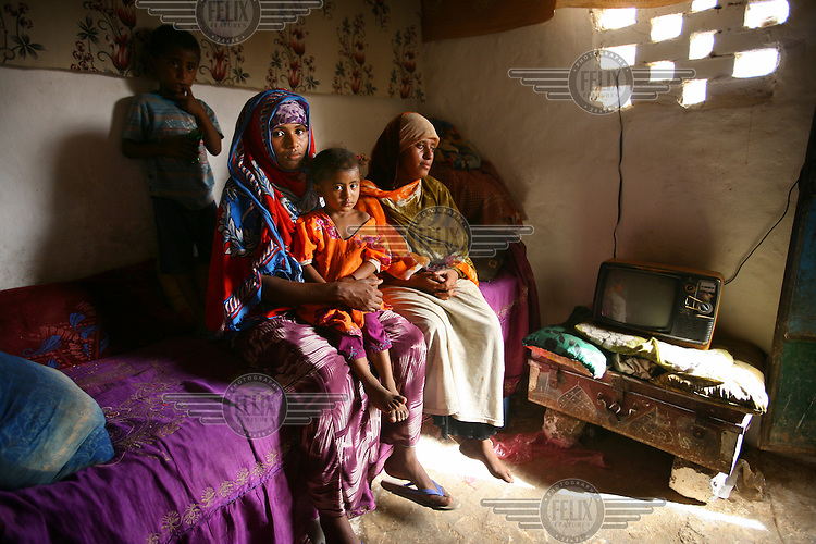 Ruqia (left) and Seloua (right) sit with Ruqia's two children, Soumaia, aged 2, and Herhan, aged 4, next to the TV in Seloua's house. Both women, now aged 18, were married at 14.