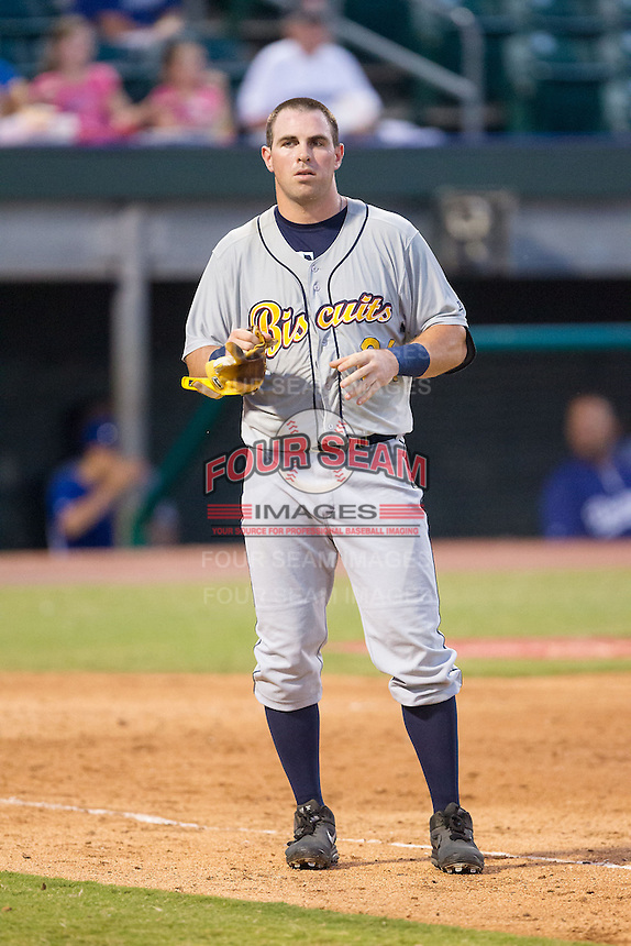Willie Argo (24) of the Montgomery Biscuits takes off his batting gloves after having made the third out of an inning during the game against the Chattanooga Lookouts at AT&T Field on July 24, 2014 in Chattanooga, Tennessee.  The Biscuits defeated the Lookouts 6-4. (Brian Westerholt/Four Seam Images)