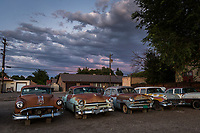 Ancient and rusting cars from half a century ago on display along a small town main street under clouds tinged with sunset's glow.