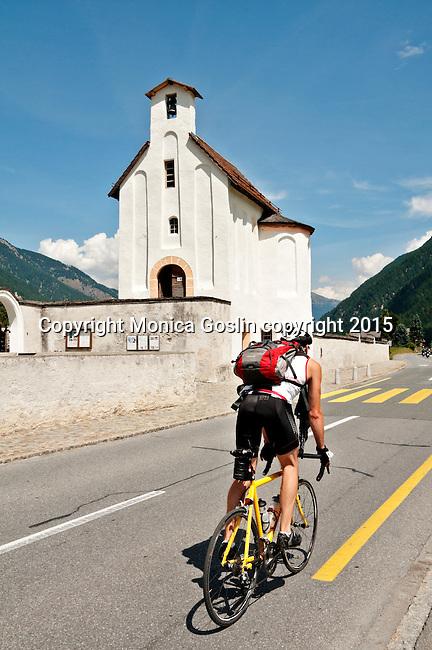 Biking on the main road, Val Mustair pass, and passing the Benedictine Convent of Saint John ; Mustair, Switzerland