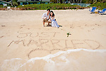 "Asian bride and groom watch a wave wash over their ""Just Married"" writing in the sand during a stroll on Lanikai beach. The couple celebrate their wedding with a honeymoon in Hawaii."