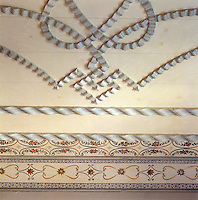Detail of the intricately carved ribbons and hand-painted frieze that decorate the ceiling of one of the bedrooms