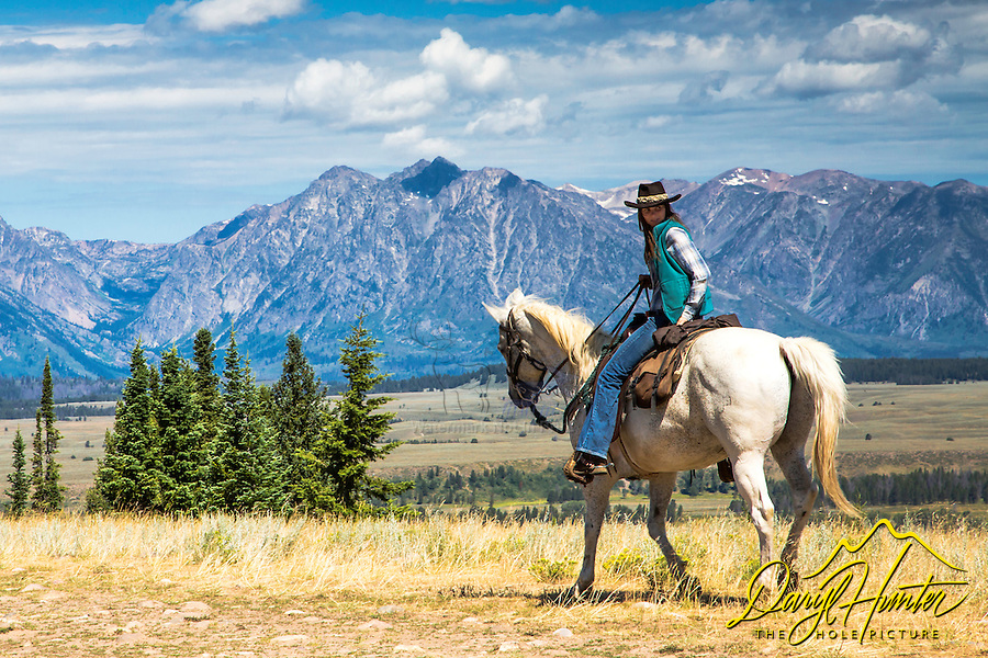 Cowgirl riding in the  Rocky Mountains