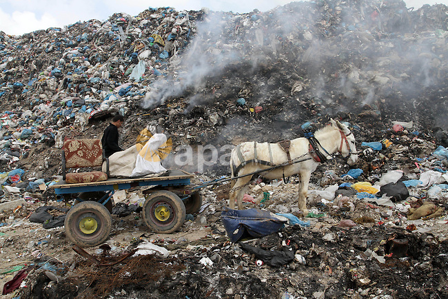A Palestinian man searches in the garbage near the border with Israel, east of Rafah town, in the southern Gaza Strip, April 16, 2015. Workers collect the household recyclables, metals and plastic from landfill and garbage to sell to the Israeli and local factories. Photo by Abed Rahim Khatib