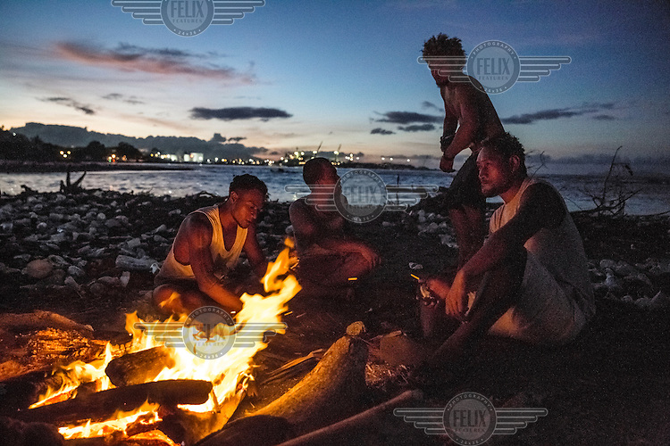Young men sit by the fire at a beach in Lord Howe Settlement, a district of the capital Honaria populated by people from Ontong Java Atoll (AKA Lord Howe Atoll), a Polynesian outlier of the Solomon Islands. Its people have been moving to Lord Howe Settlement in search of a better life since the 1970s. Climate change leading to rising sea levels and consequent food insecurity now means the atoll is existentially threatened. The remaining Ontong Javanese people are considering the possibility of complete relocation to Santa Isabel Island and to Honiara. However, with Lord Howe Settlement itself suffering the consequences of extreme weather and overcrowding, community leaders believe it is not a viable long term home. Furthermore, they fear that the Ontong Javanese people's Polynesian identity will be lost as a new generation is brought up in a location with no connection to ancestral land. Their identity will be weakened as they become a minority amongst Melanesian communities that have vastly different traditions and speak different languages.